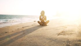 girl doing yoga on beach