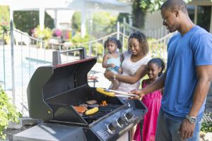 A family having a BBQ on the deck.