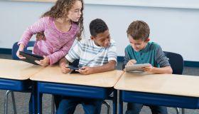 Three elementary school students, digital tablets