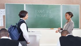 A teacher scolding a student for late arrival for the exam A