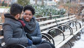 Loving Multi-Ethnic Couple sitting on a park bench