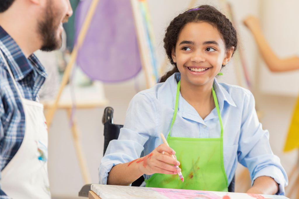 Art teacher works with preteen student