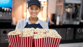 Happy woman working at the movie theatre selling popcorn