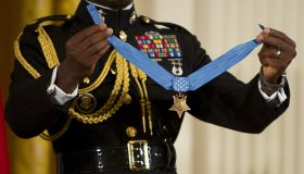 A military aide holds up the Medal of Ho