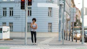 Teen girl waiting to crosswalk street at zebra crossing
