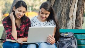 students with laptop sitting in park bench stock photo