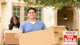 Excited young couple moves boxes into their new home.